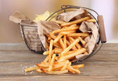 Tasty french fries and potato chips in metal baskets on wooden table, on light background — Stock Photo