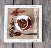 Wooden frame with white mug, coffee grains and spices on wooden background — Stok fotoğraf