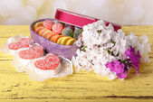 Present box with sweets and flowers on table on bright background — Φωτογραφία Αρχείου