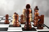 Tablero de ajedrez con piezas de ajedrez sobre fondo gris — Foto de Stock
