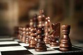 Tablero de ajedrez con piezas de ajedrez sobre fondo marrón — Foto de Stock