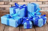 Beautiful gifts on table on brick wall background — Stock Photo