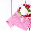 Creamy ice cream with raspberries on plate in glass bowl, on color wooden background — Stock Photo #49427439