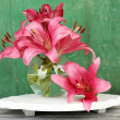 Beautiful lily in vase on wooden background — Stock Photo