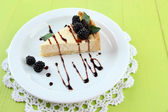 Slice of cheesecake with chocolate sauce and blackberry on plate, on wooden background — Stock Photo