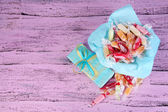 Tasty candies on paper with present on wooden background — Stock Photo