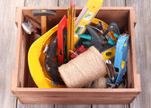 Wooden box with different tools, on wooden background — Foto de Stock