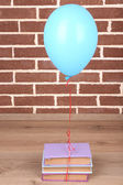 Color balloon with books on brick wall background — Stockfoto
