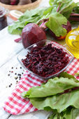 Grated beetroots in bowl on table close-up — Photo
