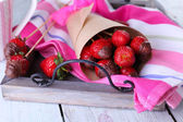Strawberry in chocolate on skewers in paper bag on table close-up — Stock Photo