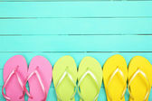 Bright flip flops on wooden background — Stock Photo