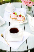 Coffee table with teacups and tasty cakes in garden — Stock Photo
