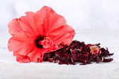 Hibiscus tea and flower on wooden table, on light background — Stock Photo