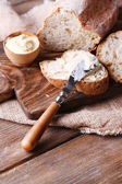 Fresh bread and homemade butter on wooden background — Stock Photo