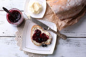 Fresh bread with homemade butter and blackcurrant jam on plate, on light wooden background — Stock Photo