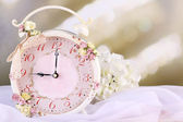 Beautiful vintage alarm clock with flowers on light background — Stock Photo