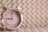 Beautiful vintage alarm clock with flowers on light background — Foto Stock