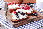 Bread with cottage cheese and berries on wooden board close-up — Stock Photo