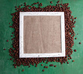 Wooden frame and coffee grains on wooden background — Foto Stock