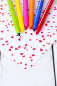 Bright markers with paper on wooden table close-up — Stockfoto