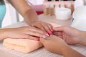 Young woman is getting manicure in beauty salon, close-up — Stock Photo