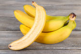 Halved and whole ripe bananas on wooden background  — Stock Photo