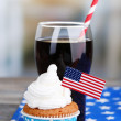 American patriotic holiday cupcake and glass of cola on wooden table — Stock Photo #49444865