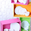 Beautiful  bright shelves and boxes with tableware  on  light wall background — Stock Photo #49453991
