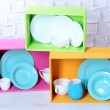 Beautiful  bright shelves and boxes with tableware  on  light wall background — Stock Photo #49453993