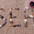 Word sea made from sea shells and stones on sand — Stock Photo #49456085