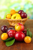 Ripe plums on wooden table on natural background — Stock Photo