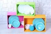 Krásné světlé police a pole s nádobí na světlé zdi pozadí — Stock fotografie