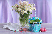 Tasty cupcake on table, on fabric background — Stock Photo