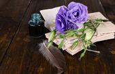 Oude brieven en bloemen op houten achtergrond close-up — Stockfoto