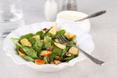 Green salad with spinach, apples, walnuts and cheese on light background — Stock Photo