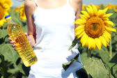 Young woman holding bottle of oil and sunflower in field — Stock Photo