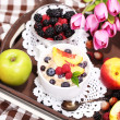 Oatmeal in plate with berries on napkins on wooden tray on bad — Stock Photo #49493341