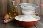 Sifting flour into bowl — Stock Photo