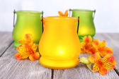 Bright icon-lamps with flowers on table on bright background — Stock Photo