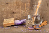 Spa still life with lavender oil and flowers on wooden table — Stock Photo