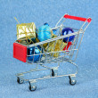 Christmas gifts in shopping trolley, on blue shiny background — Stock Photo #49526409