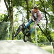 Young boy jumping with his BMX Bike at skate park — Stock Photo #49528993
