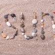 Word sun made from sea shells and stones on sand — Stock Photo #49529599