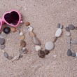 Word love made from sea shells and stones on sand — Stock Photo #49529607