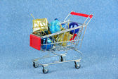 Christmas gifts in shopping trolley, on blue shiny background — Stock Photo