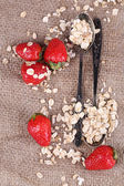 Strawberries with oatmeal and vintage spoons — Stock Photo