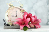 Beautiful lily with clock on wooden tray on bright background — ストック写真