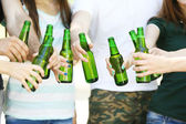 Hands holding beer bottles close up — Stock Photo