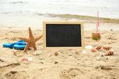 Blank chalkboard on beach background — ストック写真