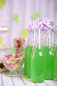 Bottles of drink with straw and sweets on decorative background — Stock Photo